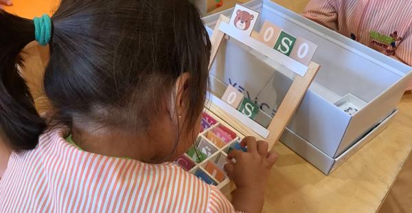 Una alumna trabaja con una caja de letras en Trastes Santiago