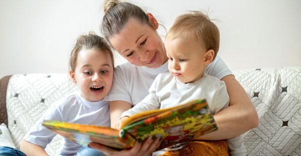 Una madre lee un cuento a sus dos hijos